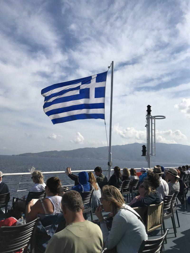 Passengers sitting on a ferry with waving Greek flag