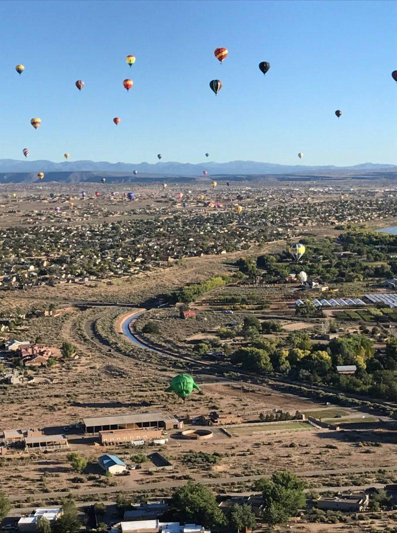 The Albuquerque International Balloon Fiesta is a bucket list item. Find out how you can book a ticket to go on a hot air balloon ride during mass ascension, with hundreds of other balloons. New Mexico is the perfect place for a hot air balloon ride. Don't go to the balloon festival without reading this post. Save to your travel board for inspiration.