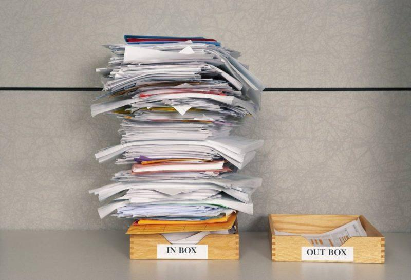 Stack of papers in inbox versus one sheet in outbox