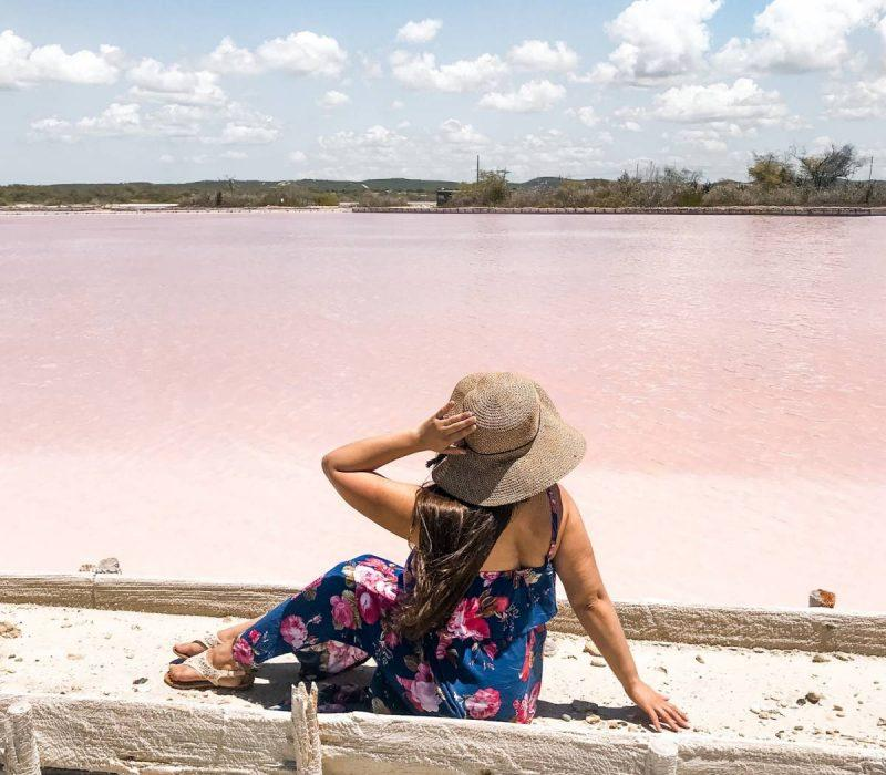 Woman sitting by pink lakes