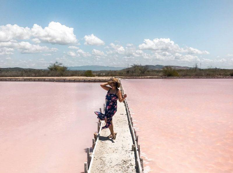 Standing by pink lakes holding hat