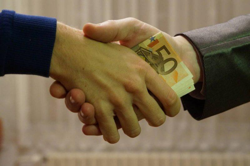 Money changing hands in handshake