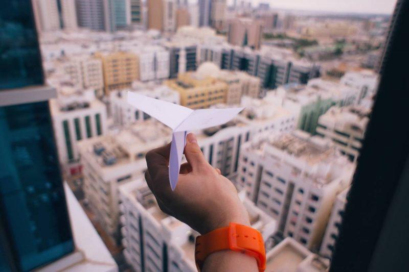 Paper airplane over buildings
