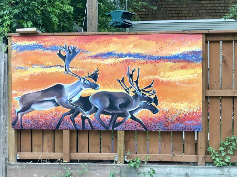 Wild caribou running at sunset