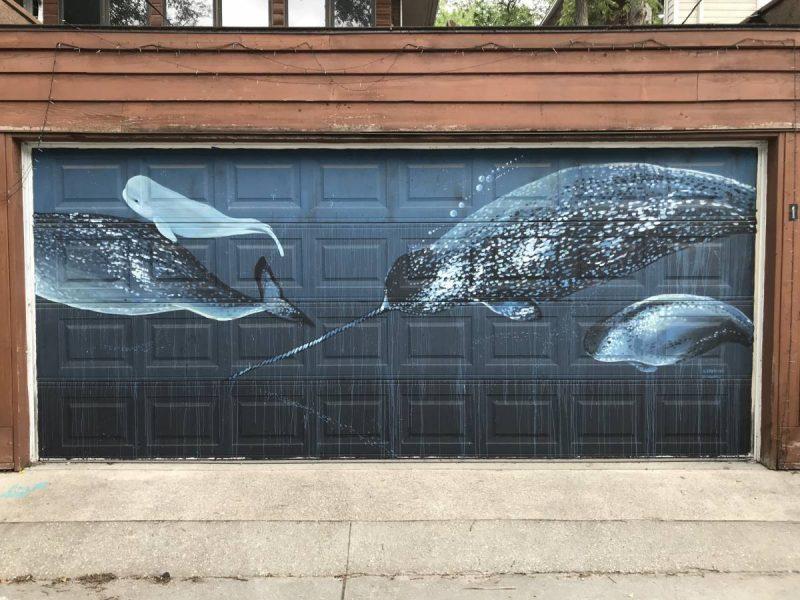 Whales swimming in the ocean painted on garage door