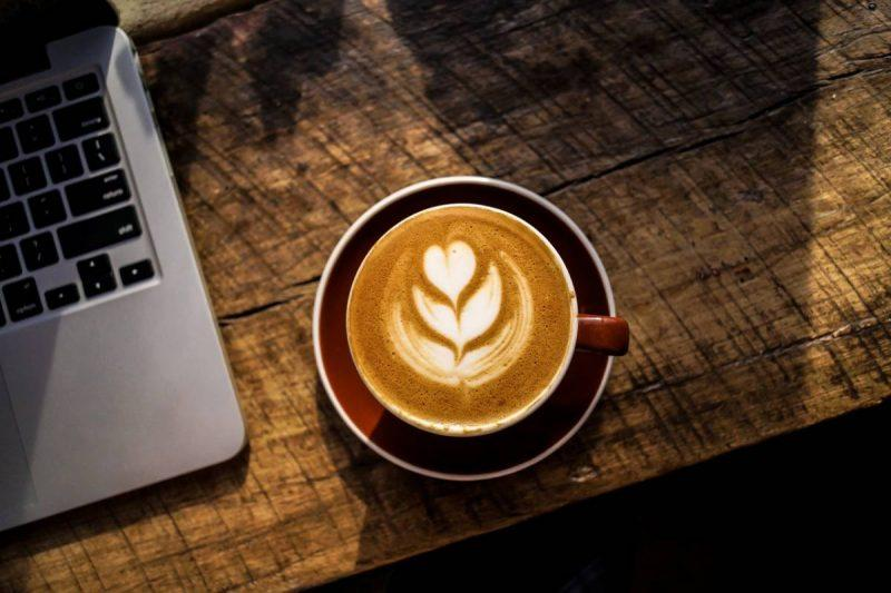 Coffee cup on a wooden table with laptop