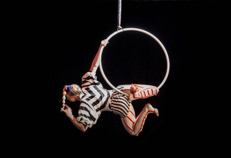Acrobat hanging from a hoop