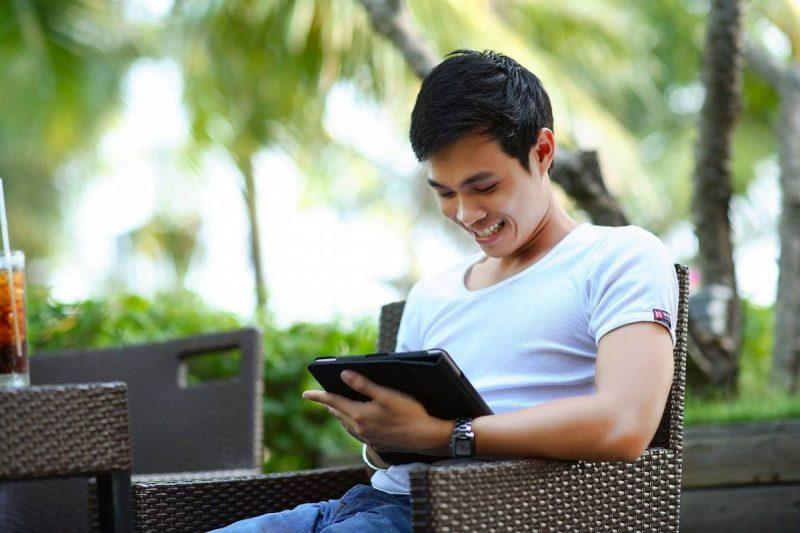 Man looking to find cheap first class tickets on tablet