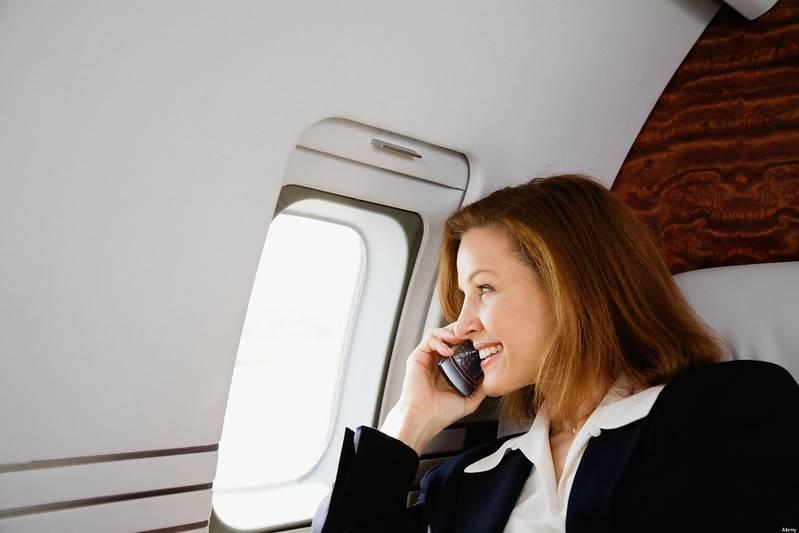 Woman talking on her phone on an airplane