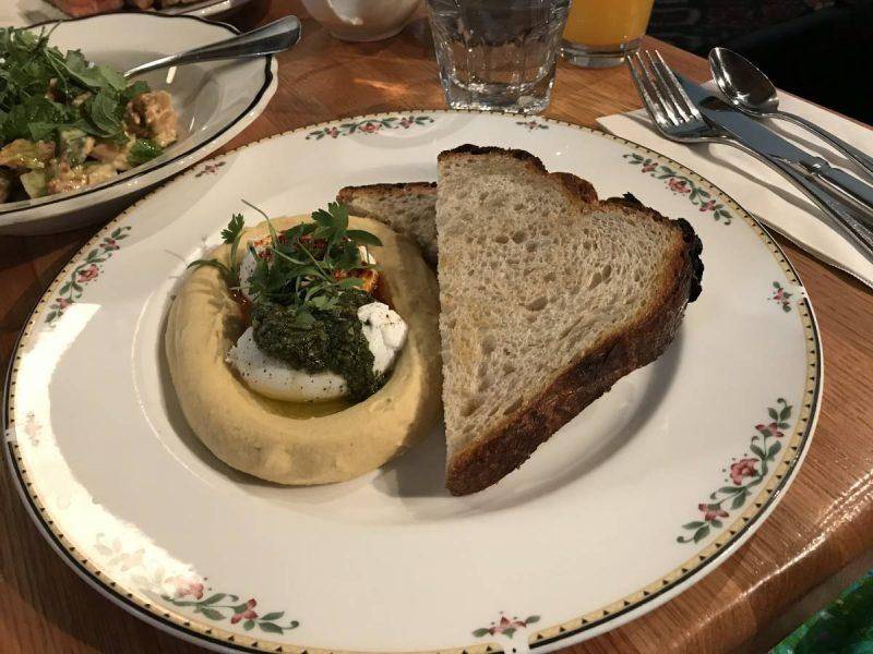 Turkish eggs on a plate with hummus and bread