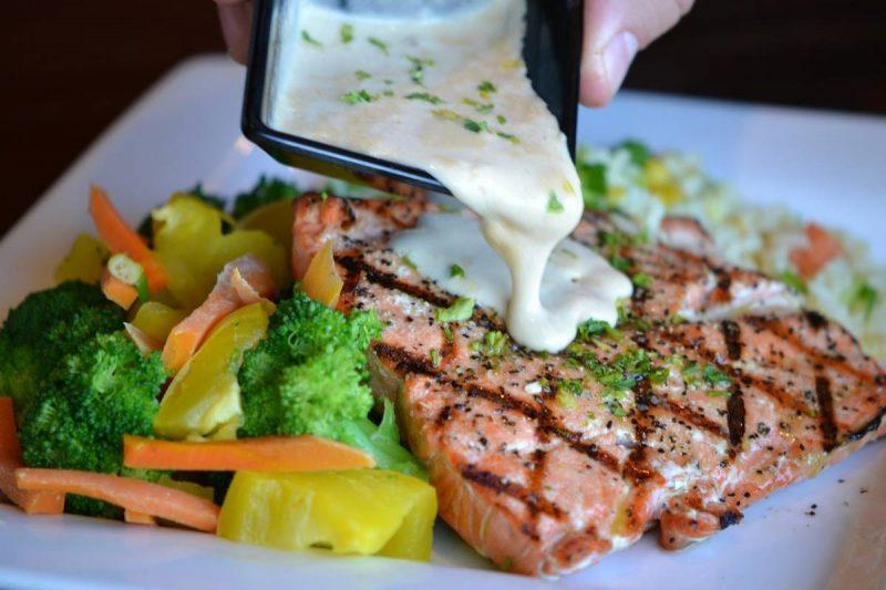 Pouring sauce over grilled salmon with a side of vegetables