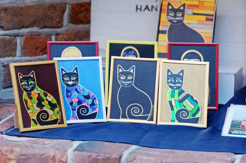 Paintings of cats on display
