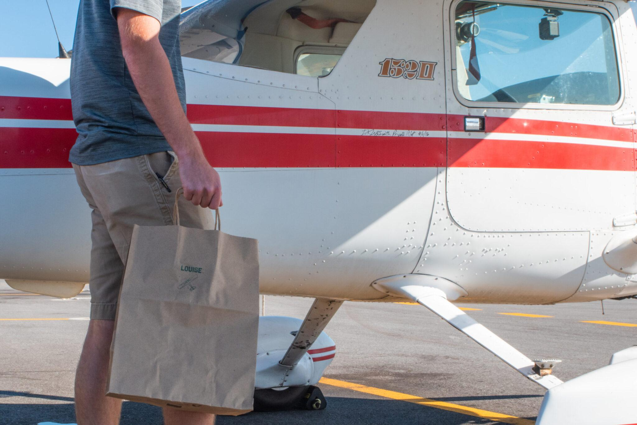 Man carrying paper bag to propeller plane