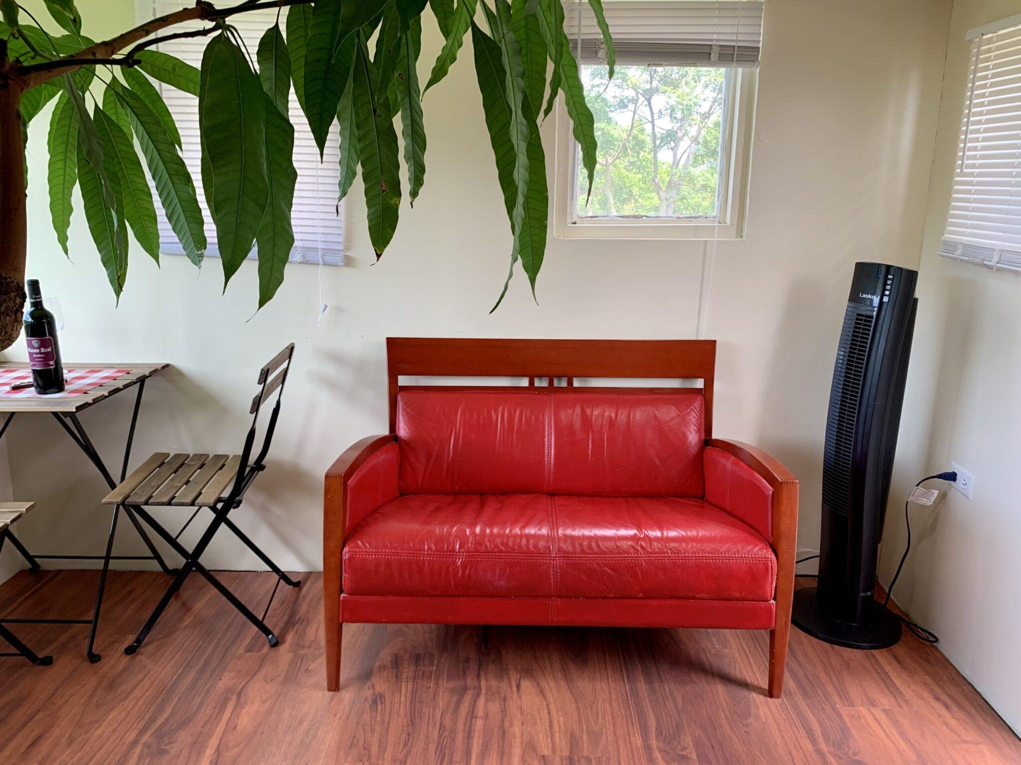 Red loveseat and dining area