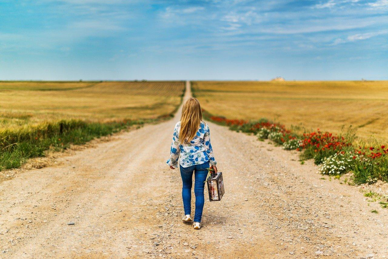 woman walking down long dirt road