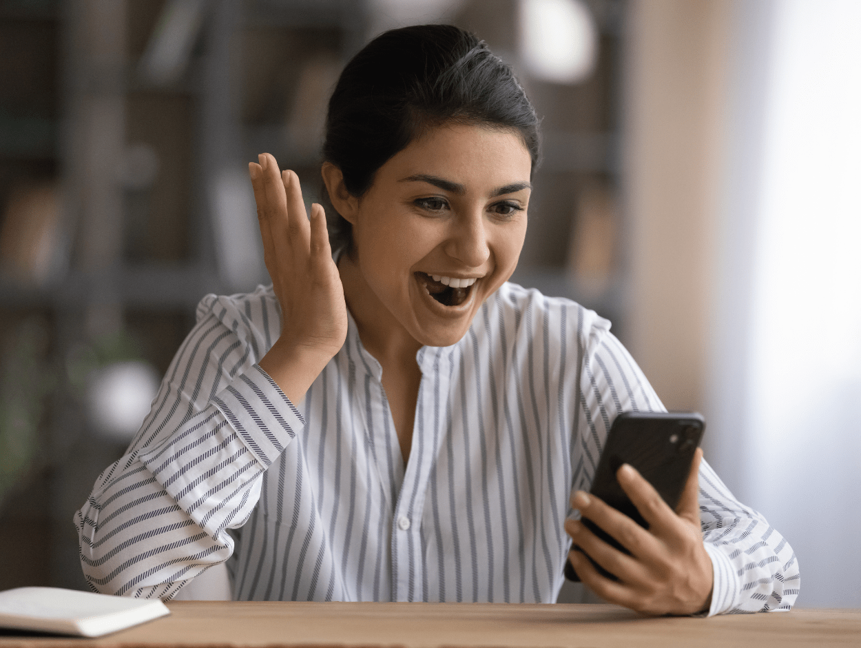 Woman excitedly looking at phone