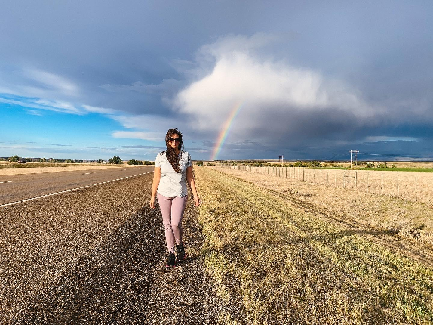 Walking roadside with a rainbow in background